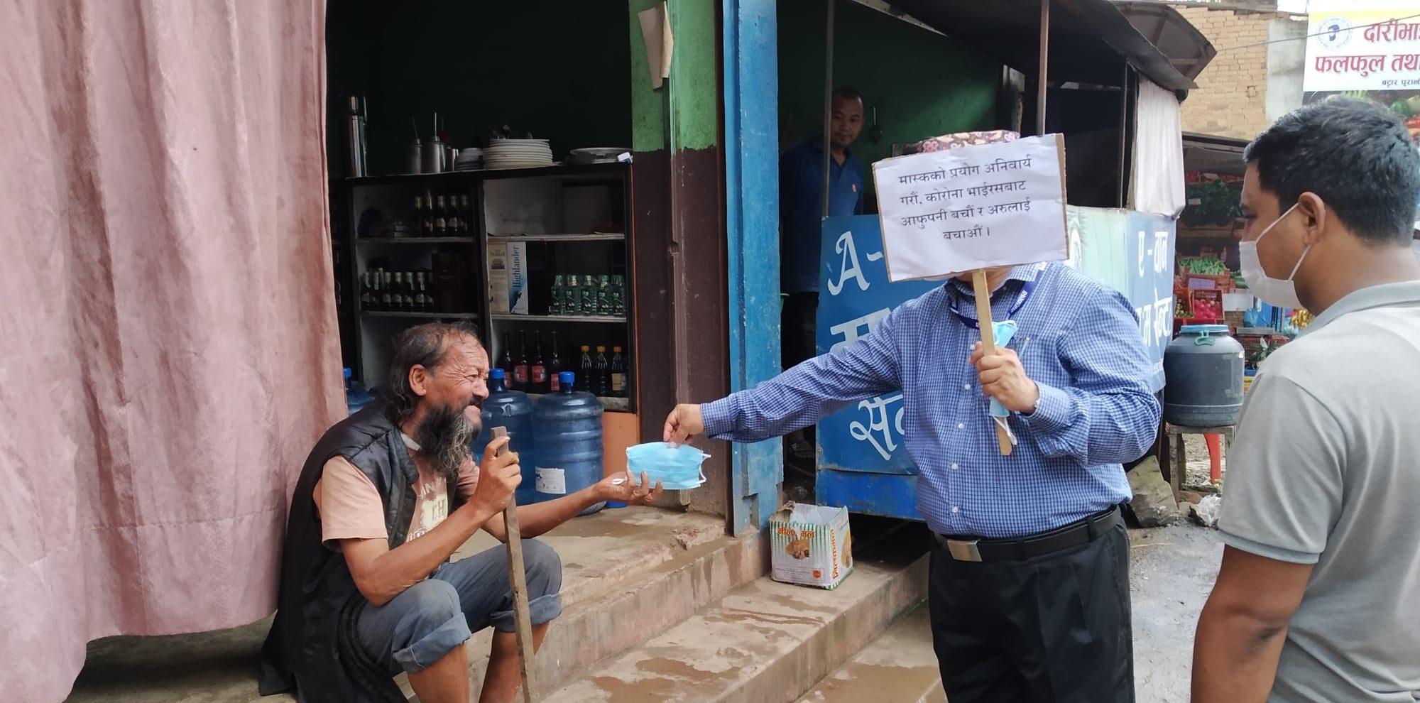cdo nuwakot jhankanath dhakal giving a mask to civil