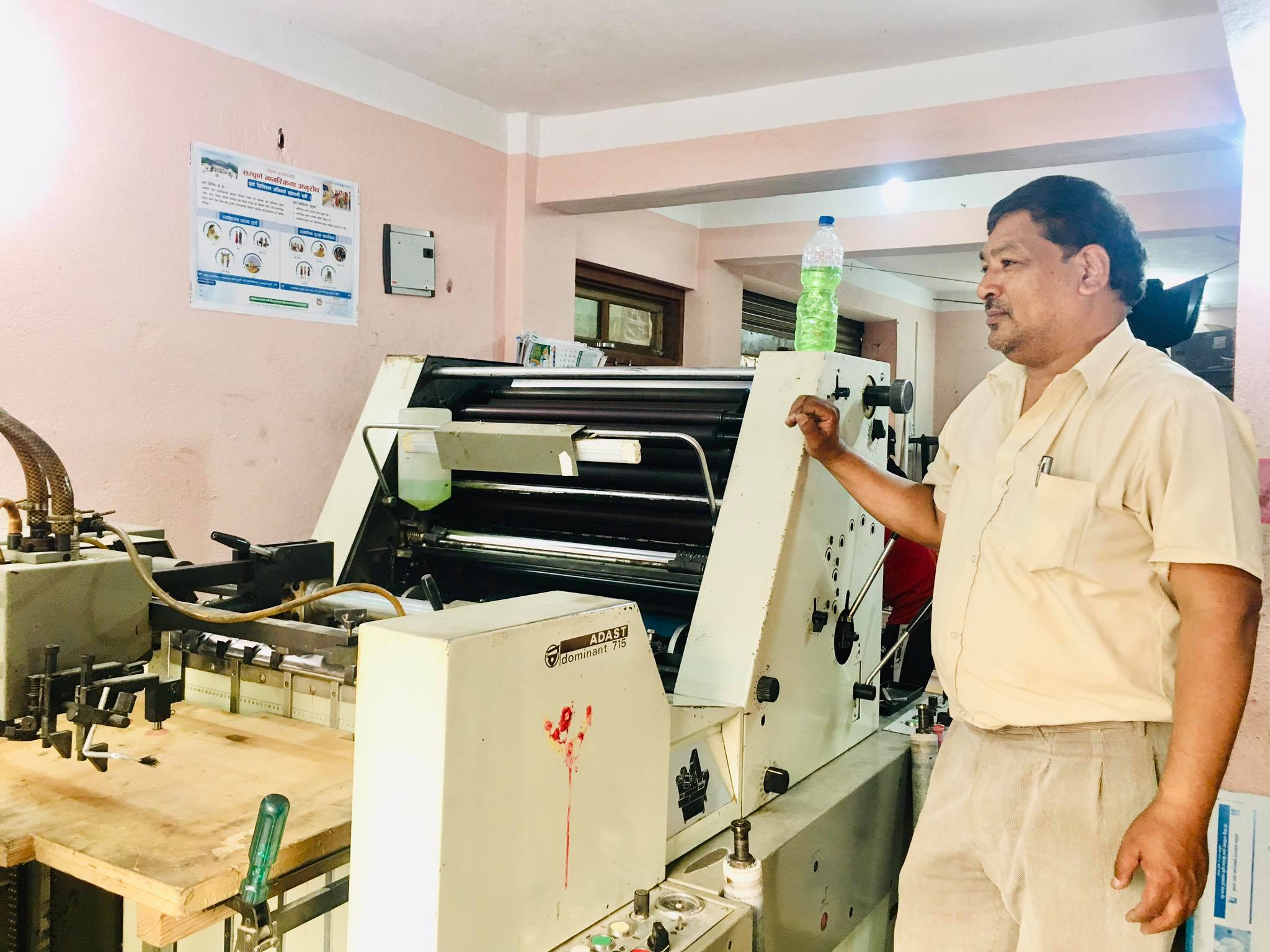 nabindra man pradhan standing in front of color offset press machine